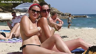 Two sexy exhibitionistic babes are flaunting their assets on the beach